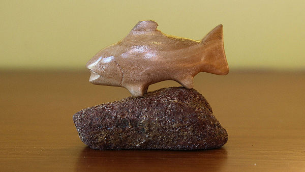 whittled fish on rock